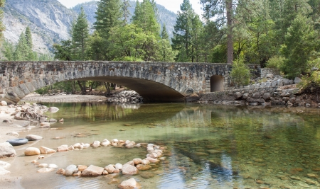 Crystal clear spring and a beautiful stone bridge in Yosemite Valley. photo