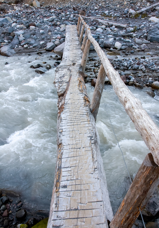 rushing water: A narrow log is set up as a foot bridge over the rushing water of the Nisqually River at Mount Ranier National Park