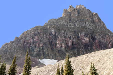 reynolds: This image of Mount Reynolds at Glacier National Park shows purple rock face and remnants of a snow field