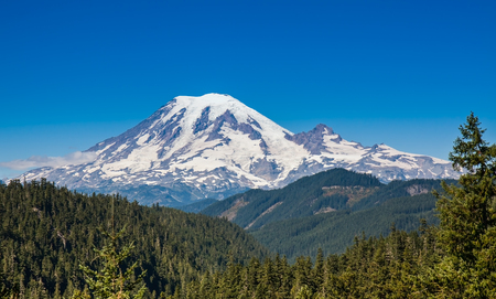 Mount Rainier towers over the surrounding mountains sitting at an elevation of 14,411 ft  It is considered to be one of the world Stock Photo