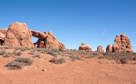 This image shows an arch and formation up a slope with a blue sky background  Taken at Arches National Park Stock Photo - 22836024
