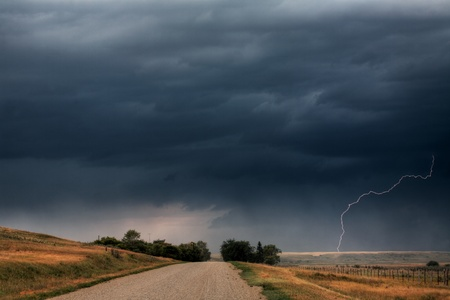 Storm clouds and lightning along a Saskatchewan country road