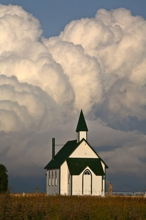 Thunderhead clouds forming behind a country church