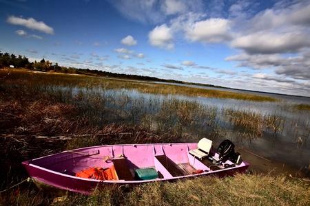 Pink boat in scenic Saskatchewan photo