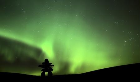 Northern light above an inukchuk in Saskatchewan Stok Fotoğraf