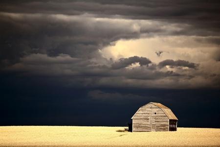 Storm clouds behind abandoned Saskatchewan barn photo
