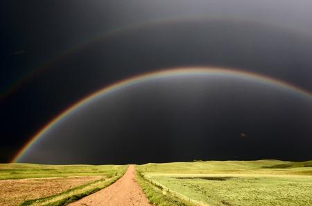 Arco iris y cielos oscuros vistos por un camino de país Foto de archivo - 8470332