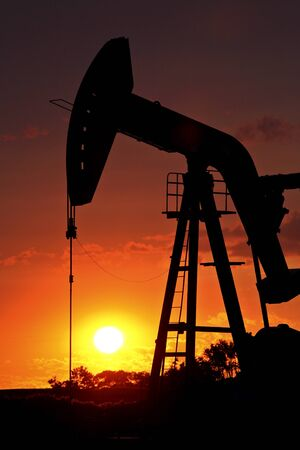 Oil rig pump jack silhouetted by setting sun Stock Photo - 8466641