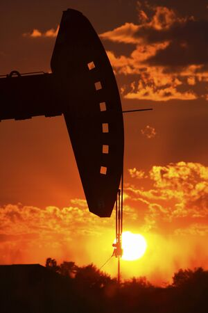 Oil rig pump jack silhouetted by setting sun Stock Photo - 8466625