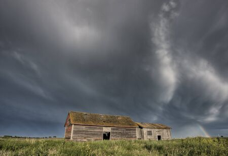 Abandoned Farm with storm clouds in the Canadian Prairie photo