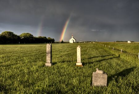Old Country Church in Saskatchewan Canada with storm clouds and rainbow photo