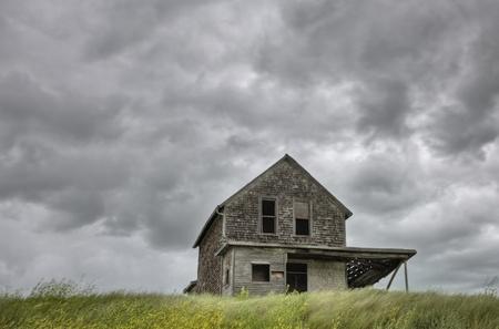 Verlaten boerderij met storm wolken in de Canadese Prairie