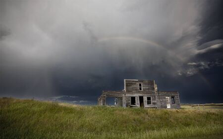Storm over abandoned farm house in Saskatchewan Canada photo