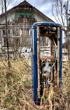 Old Vintage Gas Pump and Abandoned house photo