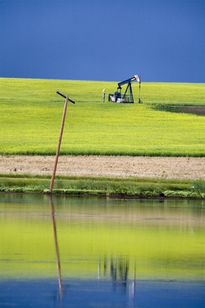 Storm Clouds Saskatchewan oil pump jack and reflection