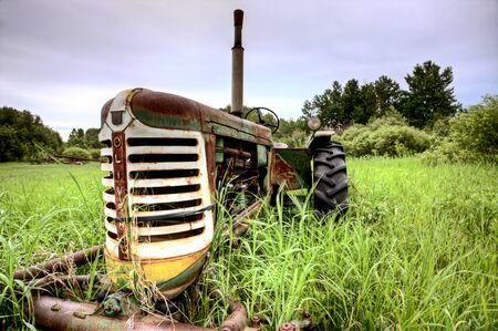 farm equipment: Old Vintage Farm Equipment in long grass Saskatchewan Canada