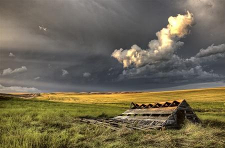 run down: Storm Clouds Saskatchewan run down abandoned building Stock Photo