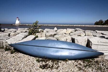 huron: Lighthouse on Lake Huron rocks and blue canoe Stock Photo