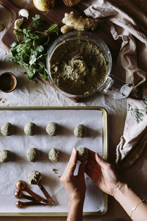 A woman is rolling curried lentil meatballs and placing them on a baking sheet before they go to the oven.