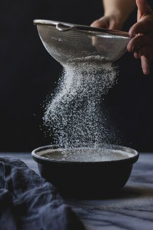 Sifting flour into a bowl whilst cooking LANG_EVOIMAGES
