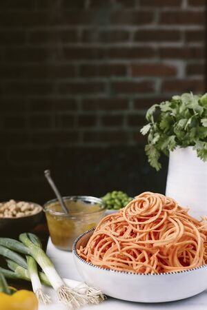 spiralized: A big bowl of spiralized sweet potato noodles are photographed from the front view along with pad thai sauce, scallions, peanuts, and cilantro.