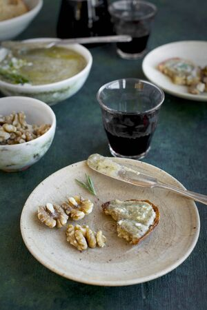 Rosemary Gorgonzola Pesto served with walnuts, crostini and red wine.  Photographed from front view on a greenblue background LANG_EVOIMAGES