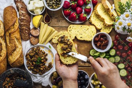 Una mujer extendiendo tapenade de oliva en una rebanada de pan de maíz. Baguette francés, salchichas, callos, queso, strawberr, es, flores, tomates y rodajas de pepino acompañan esto.