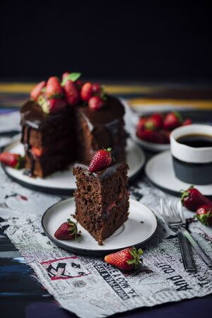 ganache: A slice of strawberry chocolate cake on the front and the whole cake and a cup of tea on the back.