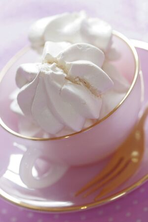 Sweet cakes from a patisserie. Meringue in a pink cup and saucer with fork.