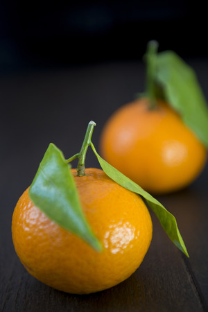 clementines: Clementine oranges on a wooden board.  North African variety of tangerine which is grown around the Mediterranean and in South Africa. LANG_EVOIMAGES