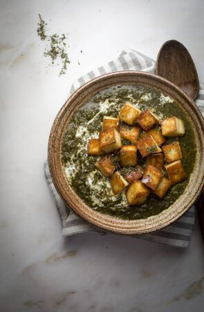 Palak paneer  creamy cottage cheese spinach curry in a ceramic bowl