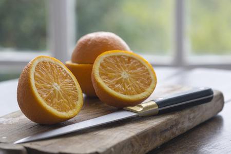 Cut oranges on wood baord on table against window framed garden background
