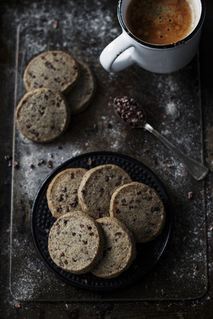 enriched: Delicious sable cookies with buckwheat flour, enriched with cocoa nibs. Set up on a dark vintage background