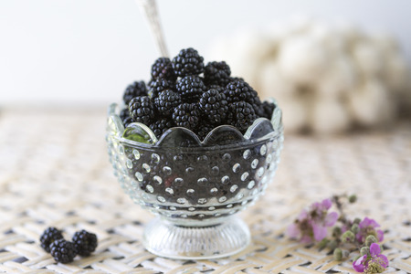 vintage: blackberries in glass dish on woven tray with vintage spoon