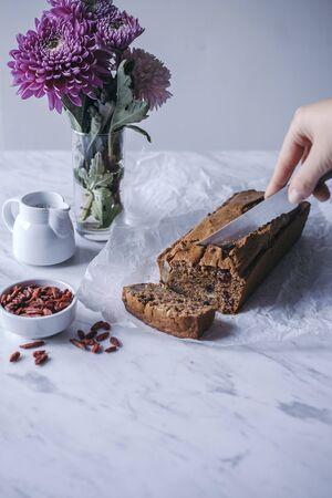 Woman cutting through a loaf of healthy vegan fruit bread