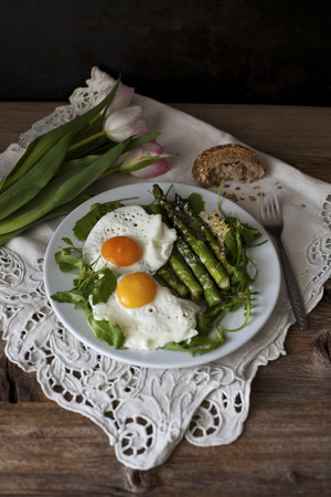 Roasted asparagus with Parmesan cheese on a bed of rucola salad and topped with fried eggs