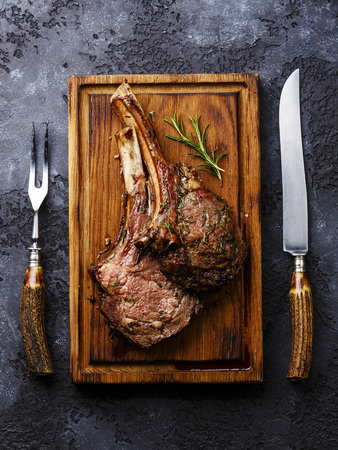 trinchante: Roasted beef ribs on bone on wooden cutting board with knife and fork carving set on dark background