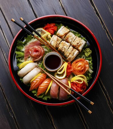 Sushi Set nigiri, rolls and sashimi served in traditional Japan black Sushioke round plate