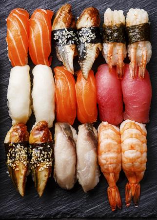 Nigiri sushi set on black stone slate close up