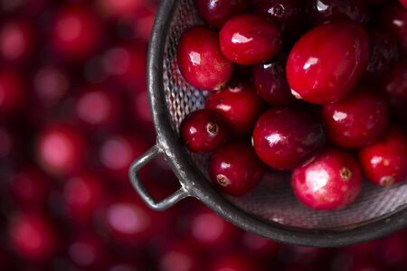 Macro shot of cranberries in a vintage, metal strainer with more cranberries in background.