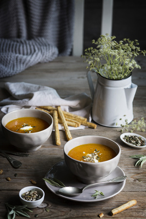 gressins: Pumpkin cream soup in grey bowls on rustic wooden table