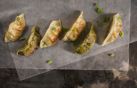 potstickers: A variety of pan seared pork and vegetable pot stickers on wax paper on a rustic metal surface with fresh green onions.