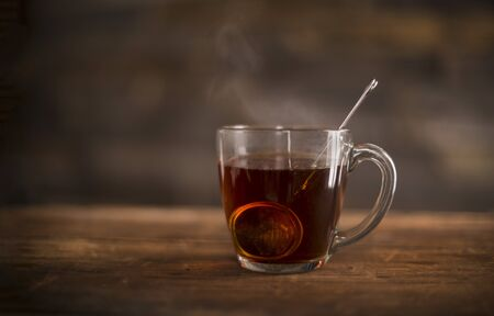 Clear glass of steaming hot tea with infuser on wooden, rustic suface.
