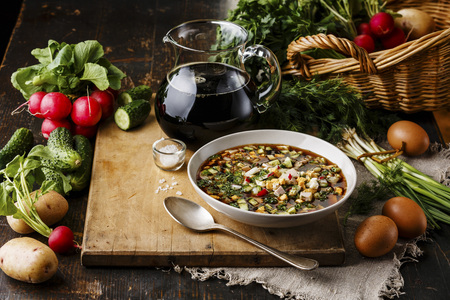 okroshka: Cold Soup Okroshka with sausage, vegetables and kvass serving size in bowl and raw ingredients on wooden table