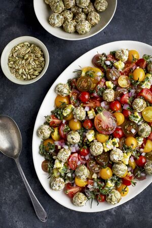 white wine: Heirloom Cherry Tomato Salad with Toasted Seeded Chevre served with white wine and crusty bread. Photograpghed from top view on a blackgrey background.