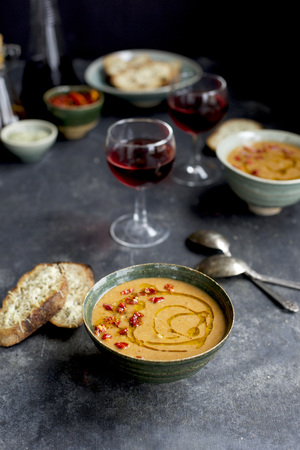 white wine: Sun-dried Tomato Pesto White Bean Soup topped with sun-dried tomato and chili oil in a ceramic bowl with Asiago Crostini and red wine.  On a blackgrey background.  Photographed from front view. LANG_EVOIMAGES