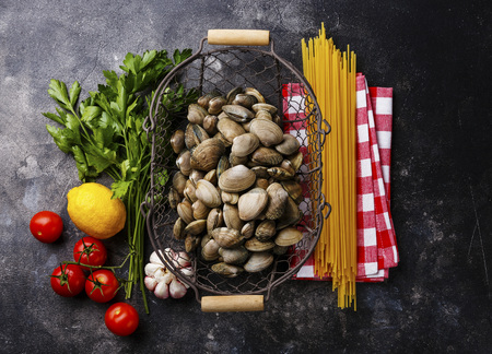Raw food Ingredients for cooking Spaghetti alle vongole on dark background