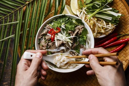 Pho Bo Soup with beef and chopsticks in male hands close-up LANG_EVOIMAGES