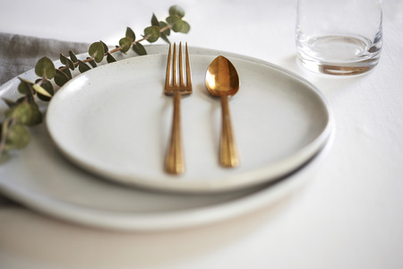 Minimal table setting with handmade off-white plates, gold silverware and linens.
