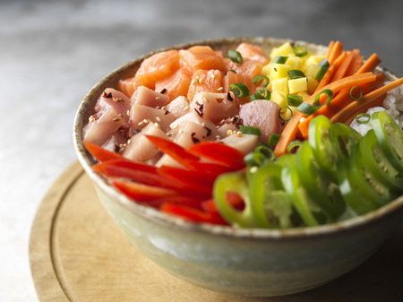 Detail image of sushi bowl with fresh salmon, tuna and crisp cut vegetables.